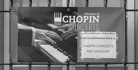 Sign on an iron fence showing a close-up of hands playing piano. The sign advertises The best of Chopin Concerts. A white piece of paper is taped to the sign. It states, Due to coronavirus, Chopin Concerts are canceled