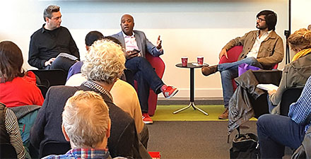 Candid's Joey Guastella (on the left in a dark shirt, looking at the speaker) leads a panel discussion at Candid during Arts Month in 2019