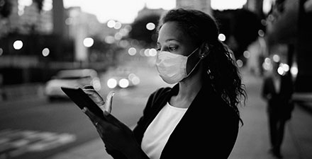 A woman wearing a medical mask looks at her cellphone