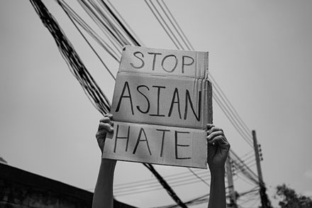 Hands holding a cardboard sign stating, Stop Asian Hate.